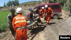 Nhân viên cứu hỏa khiêng một phụ nữ bị thương sau trận động đất mạnh tại tỉnh Cam Túc, Trung Quốc, ngày 22/7/2013.
