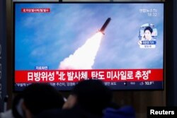 FILE - People in Seoul, South Korea, watch a TV broadcasting file footage for a news report on North Korea firing an unidentified projectile, Nov. 28, 2019.