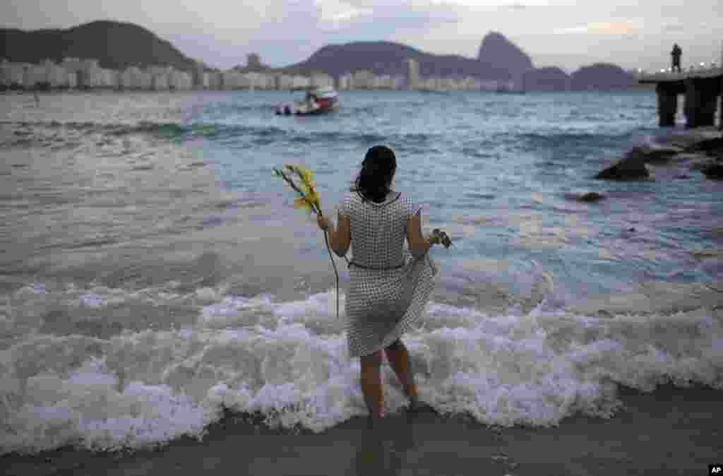 A woman offers flowers to Yemanja, goddess of the sea, for good luck in the coming year during New Year's Eve festivities on Copacabana beach in Rio de Janeiro, Brazil, Dec. 31, 2016.