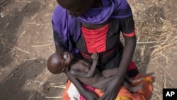 FILE - Adel Bol, 20, cradles her 10-month-old daughter at a food distribution site in Malualkuel in the Northern Bahr el Ghazal region of South Sudan, April 5, 2017.