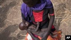 Adel Bol, 20 ans, berce sa fille de 10 mois, Akir Mayen, à Malualkuel dans la région de Bahr el Ghazal au Soudan du sud.