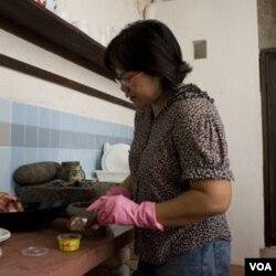 Nazlina Hussin mempersiapkan bahan untuk kelas memasak yang diadakan di sebuah ruko sewaan yang telah berdiri sebelum perang di Georgetown, Penang.