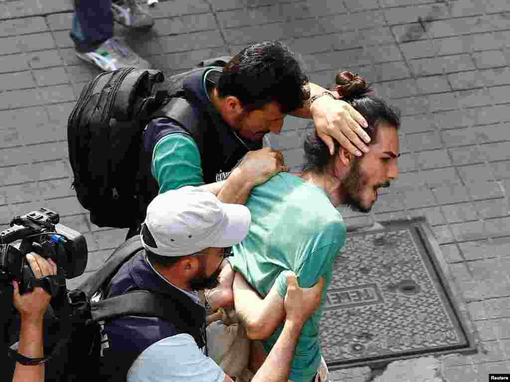 ប៉ូលិសស្លៀកពាក់ឯកសណ្ឋានស៊ីវិលឃាត់ខ្លួនសកម្មជនលើសិទ្ធិរបស់ក្រុមអ្នកស្រឡាញ់ភេទដូចគ្នា នៅពេលពួកគេប្រមូលផ្តុំសម្រាប់ការដើរក្បួនមួយនៅក្នុងក្រុង Istanbul ប្រទេសតួកគី។