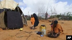 A Somali woman from southern Somalia, washes clothes outside her makeshift shelter in a refugee camp in Mogadishu, Somalia, August 4, 2011