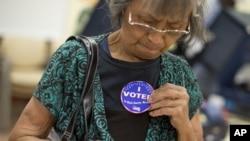 La hispana Aida Castillo muestra el distintivo de haber votado durante el sufragio temprano en Las Vegas, Nevada.