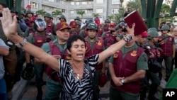 Una mujer ora, biblia en mano, frente a guardias bolivarianos, durante una protesta en Plaza Altamira, Caracas.