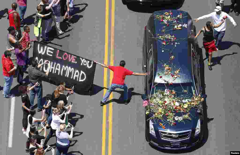 A well-wisher holding a banner touches hearse carrying remains of Muhammad Ali during funeral procession for the three-time heavyweight boxing champion in Louisville, Kentucky, June 10, 2016.