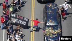 Seorang pelayat memegang spanduk berusaha menyentuh mobil yang mengangkut peti jenazah Muhammad Ali selama prosesi pemakaman legendaris tinju dunia tersebut di Louisville, Kentucky (10/6).