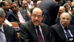 Iraqi Prime Minister Nouri al-Maliki, center, attends the first session of parliament in the heavily fortified Green Zone in Baghdad, Iraq, July 1, 2014.