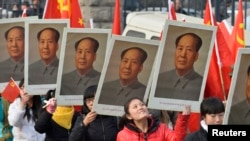 中国山西省太原一所大学的学生手举中共前领导人毛泽东的画像庆祝毛泽东诞辰120周年。(资料照片)