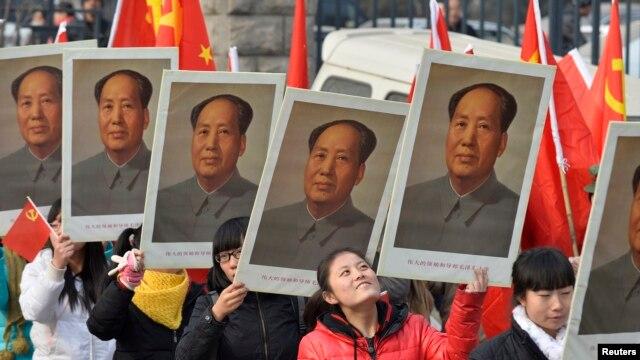 中国山西省太原一所大学的学生手举中共前领导人毛泽东的画像庆祝毛泽东诞辰120周年。(2013年12月21日)