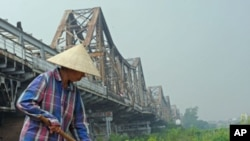 A farmer works in a field below the historical Long Bien bridge, in Hanoi, Vietnam, October 2009. (file photo)