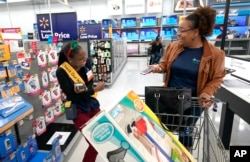 "Fast Checkout-Holiday: Walmart associate Shanay Bishop, left, checks out customer Carolyn Sarpy on the sales floor as part of the ""Check Out With Me"" program at a Walmart Supercenter in Houston, Nov. 9, 2018."