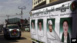 Members of the Union Solidarity and Development Party drive a campaign vehicle with posters of the party's candidates who are running in the Nov. 7 general elections in Yangon, Burma, 31 Oct 2010