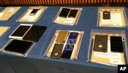 A collection of Apple iPhones and iPads fill a table during a news conference at New York City Police Headquarters, Feb. 18, 2016. Police and prosecutors in New York City said Thursday that the top-notch encryption technology on Apple mobile phones is no