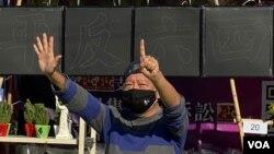 """香港支聯會主席李卓人不滿食環署終止維園年宵攤檔合約,高舉反送中運動""""五大訴求、缺一不可""""的抗議手勢。(美國之音 湯惠芸拍攝)"""