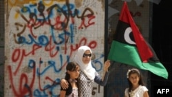 A Libyan woman holding the rebellion's flag tours with her daughters Muammar Gadhafi's destroyed headquarters of Bab al-Aziziya in Tripoli, August 31, 2011