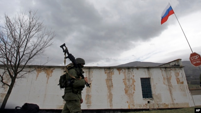 A Russian soldier marches as he and comrades block the Ukrainian infantry base in Perevalne, Ukraine, March 4, 2014.