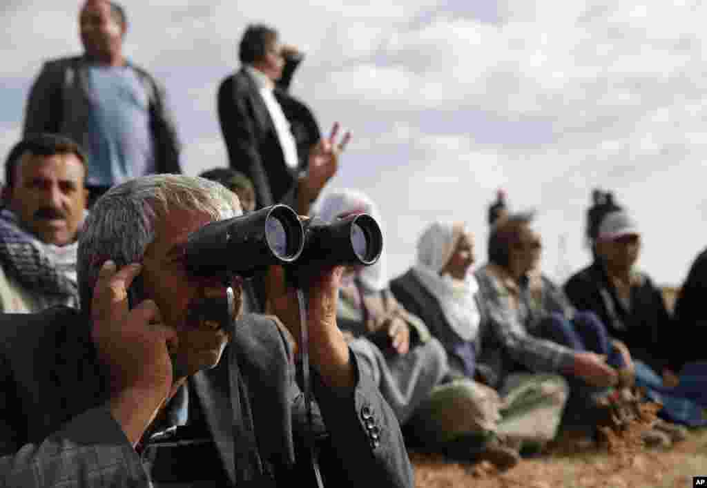 People gather on a hilltop on the outskirts of Suruc, at the Turkey-Syria border, to watch fighting between Syrian Kurds and the Islamic State militants, Syria, Oct. 15, 2014.