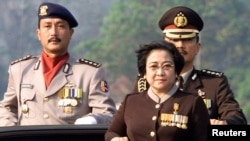 FILE - Indonesian President Megawati Sukarnoputri, flanked by her adjutant Colonel Budi Gunawan (R) and ceremony commander Police Commissioner Sunaryono (L) at the 56th anniversary of the country's police force in Jakarta, July 1, 2002.
