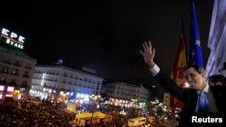 Venezuelan opposition leader Juan Guaido gestures toward supporters from the balcony of the headquarters of Madrid's regional government in Madrid, Spain, Jan. 25, 2020.