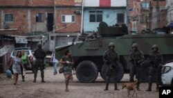 Brazilian marines stand in guard next to an armored vehicle a during surprise operation in Kelson's slum in Rio de Janeiro, Feb. 20, 2018.