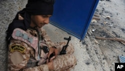 FILE - A Libyan soldier reloads his weapon during clashes with Islamist militias in Benghazi, Libya.