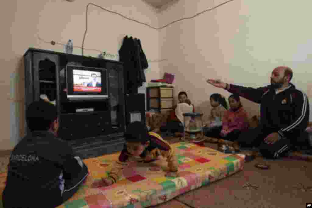 Syrian refugees who fled the violence in Syria watch Syria's President Bashar al-Assad speaking in Damascus, on a television at their temporary home at Al Hussein Palestinian refugees camp in Amman January 10, 2012.
