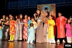 Các em thiếu nhi cùng các anh chị biểu diễn văn nghệ, trình diễn áo dài trên sân khấu Hội chợ Tết do Nhà Việt Nam tổ chức ở bang Virginia, ngày 28/1/2017. (Hình: Trà Mi)