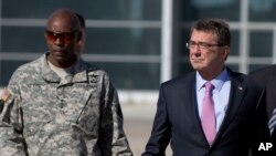 FILE - U.S. Army Lt. Gen. Ron Lewis, left, is pictured with U.S. Defense Secretary Ash Carter at Queen Alia Airport in Amman, Jordan, July 24, 2015.