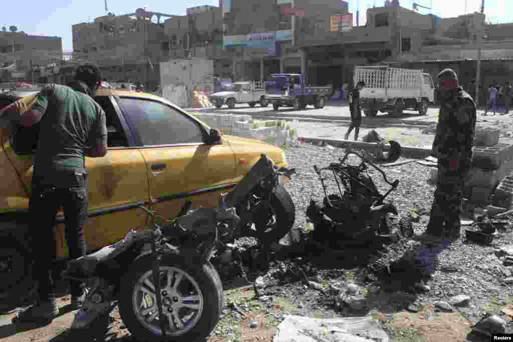 A police officer examines a vehicle that was used in a car bombing in Baghdad's Sadr City, Sept. 30, 2013.