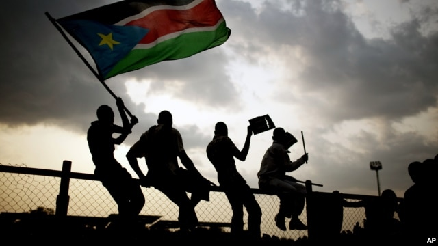 Southern Sudanese wave flags and cheer at the Republic of South Sudan's first national soccer match in the capital of Juba, July 10, 2011.