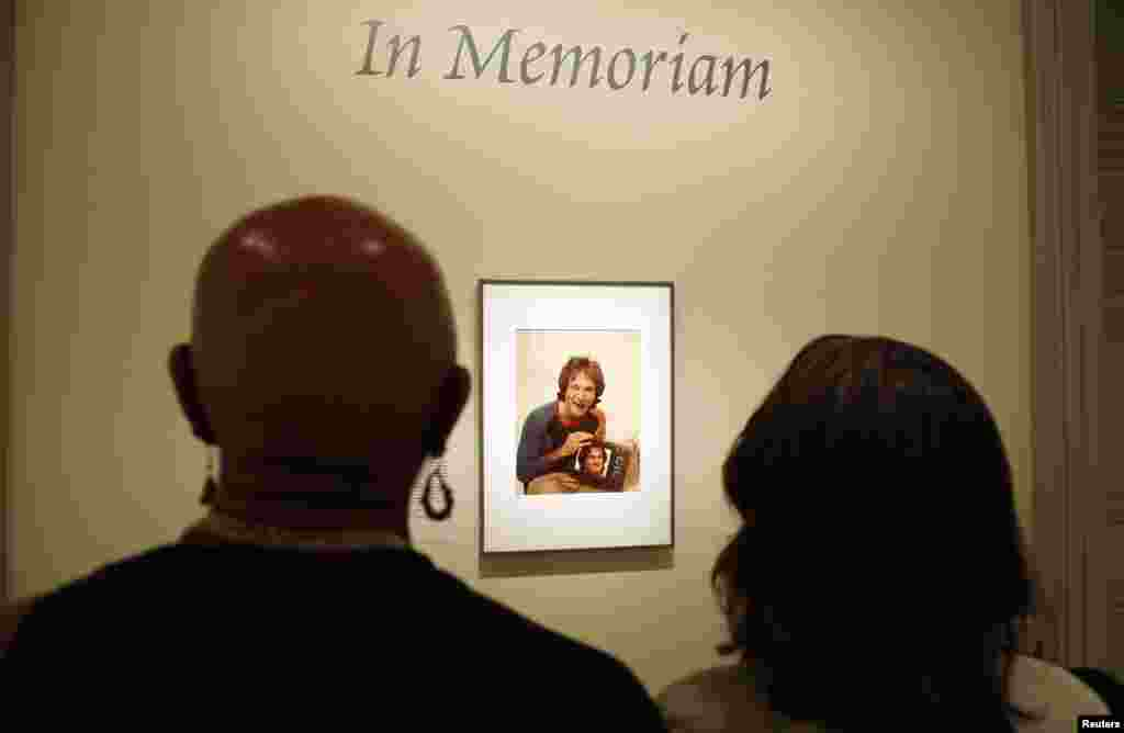 Visitors look at a photograph of Oscar-winning actor and renowned comedian Robin Williams displayed at the Smithsonian's National Portrait Gallery in Washington, D.C., Aug. 12, 2014.