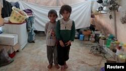 Des frères et sœurs syriens, déplacés de l'est de la province d'Idlib, posent pour une photo dans une tente du camp d'Atmeh en Syrie, près de la frontière turque, le 19 juin 2020.