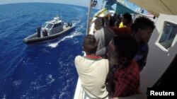 Migrants are seen on the ship Lifeline while the Malta Armed Forces arrive to send aid, near Malta in international waters June 23, 2018, in this still image taken from a video obtained from social media.