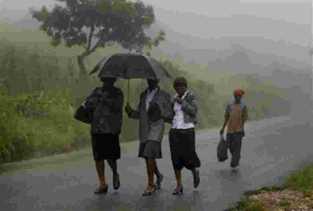 La gente camina en el camino entre Gonaives y Cabo Haitiano, bajo la lluvia de las bandas exteriores del huracán Irene en Haití, 23 de agosto de 2011.