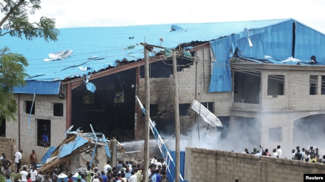 Onlookers gather near the bomb-damaged Shalom Church in the northern Nigerian city of Kaduna, June 17, 2012.