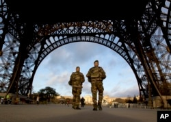 French soldiers patrol at the Eiffel Tower which remained closed on the first of three days of national mourning in Paris, Nov. 15, 2015.
