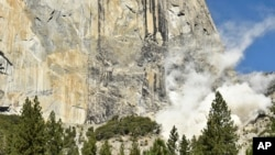 A cloud of dust rises at the base of El Capitan after a rock fall in Yosemite National Park, Calif., Sept. 27, 2107. An official said a British climber was killed an another injured in Wednesday's rock fall.