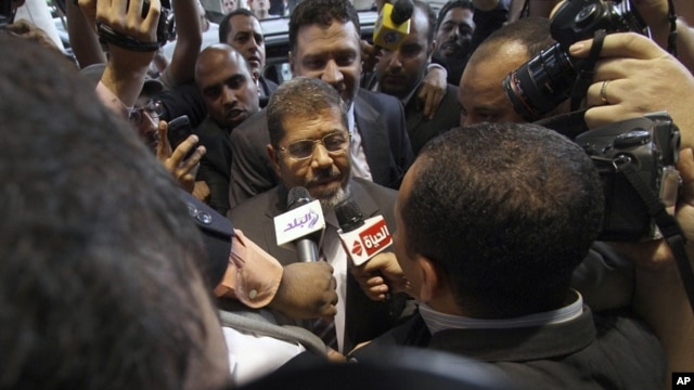 Mohamed Morsi, the Muslim Brotherhood's presidential candidate, is surrounded by reporters in Cairo, Egypt, May 26, 2012.