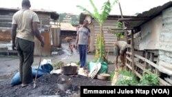 Troisjeunes à côté de leur atelier de fabrication des cocottes en aluminium à Yaoundé, le 16 novembre 2017. (VOA/Emmanuel Jules Ntap)