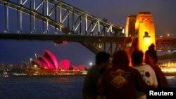 Sekelompok orang duduk di depan Gedung Opera Sydney yang diterangi lampu pink untuk menandai undang-undang pernikahan sesama jenis yang ditandatangani minggu ini di Sydney, Australia, 8 Desember 2017.