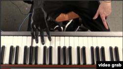 Jason Barnes, yang kehilangan tangan kanannya, kini dapat memainkan tuts-tuts piano dengan jari-jari prostetiknya. (Foto: VOA/videograb)