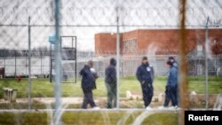 FILE - Inmates exercise in the yard at the Marion Correctional Institution, where there have been positive cases of the coronavirus disease, in Marion, Ohio, April 22, 2020.