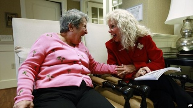 File -  Alexis McKenzie, right, executive director of The Methodist Home of the District of Columbia Forest Side, an Alzheimer's assisted-living facility, shares a light moment with resident Catherine Peake, in Washington, February 6, 2012.