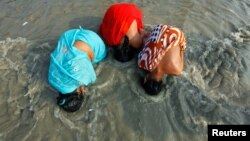 Các phụ nữ đạo Hindu đi hành hương nhúng đầu xuống nước sông Hằng
