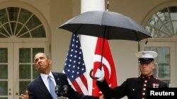 지난 2013년 미 해병대원이 바락 오바마 당시 대통령을 위해 우산을 받쳐 들고 있다.