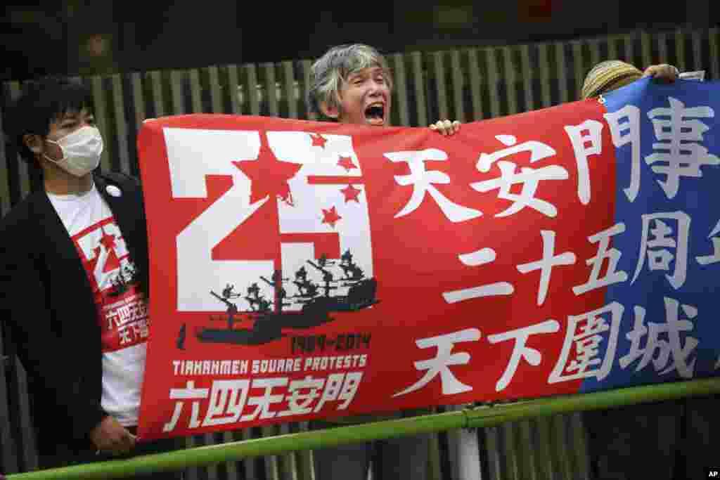 Seorang demonstran membentangkan spanduk sementara beberapa demonstran lainnya meneriakkan slogan di depan Kedubes China di Tokyo, Jepang (4/6).