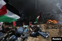 Palestinian demonstrators take cover from Israeli fire and tear gas during a protest against U.S. embassy move to Jerusalem and ahead of the 70th anniversary of Nakba, at the Israel-Gaza border in the southern Gaza Strip, May 14, 2018.