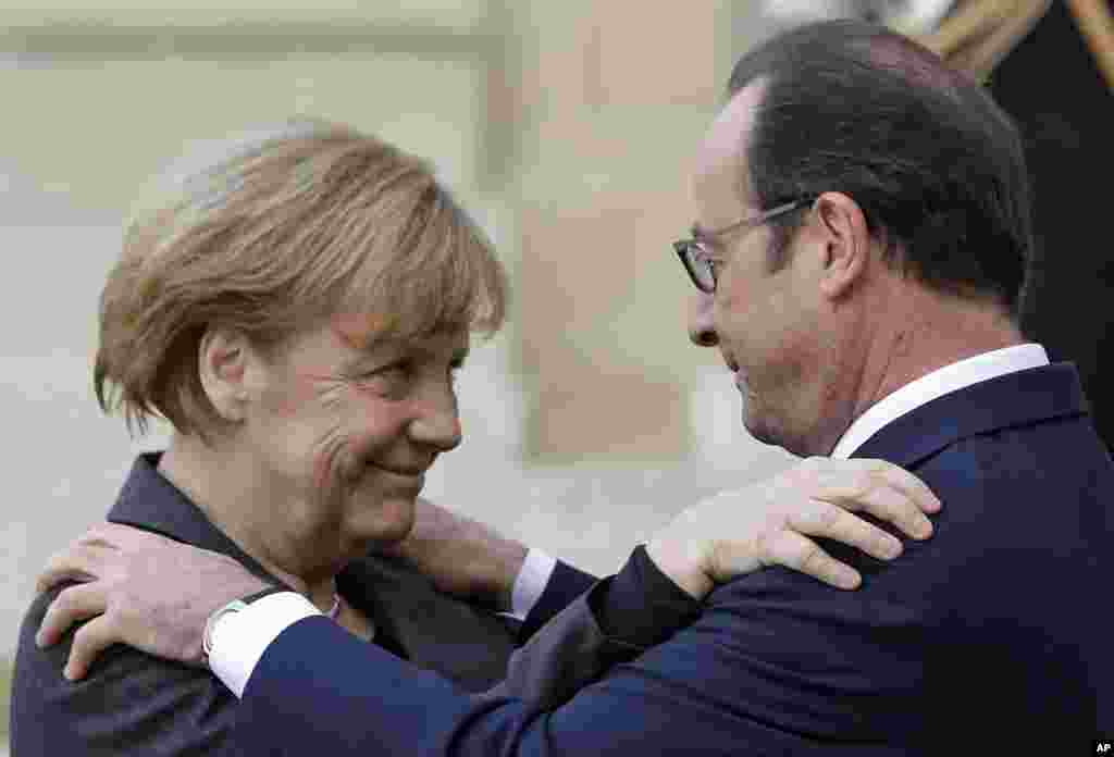 French President Francois Hollande embraces German Chancellor Angela Merkel, left, as she arrives at the Elysee Palace, Paris, Jan. 11, 2015.